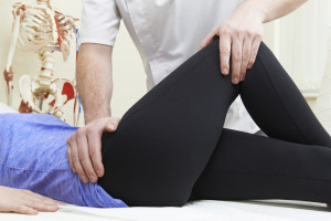 Physical therapist assists patient after artificial hip surgery