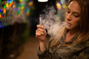 Young woman using vaping product